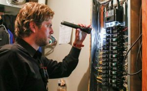 Lars Knobloch doing a thorough home inspection with a flashlight